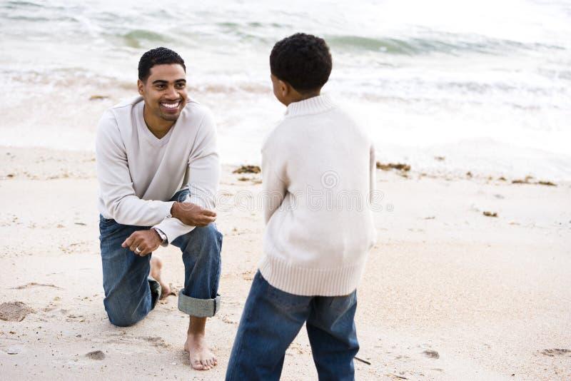 Padre e hijo del African-American que juegan en la playa foto de archivo libre de regalías