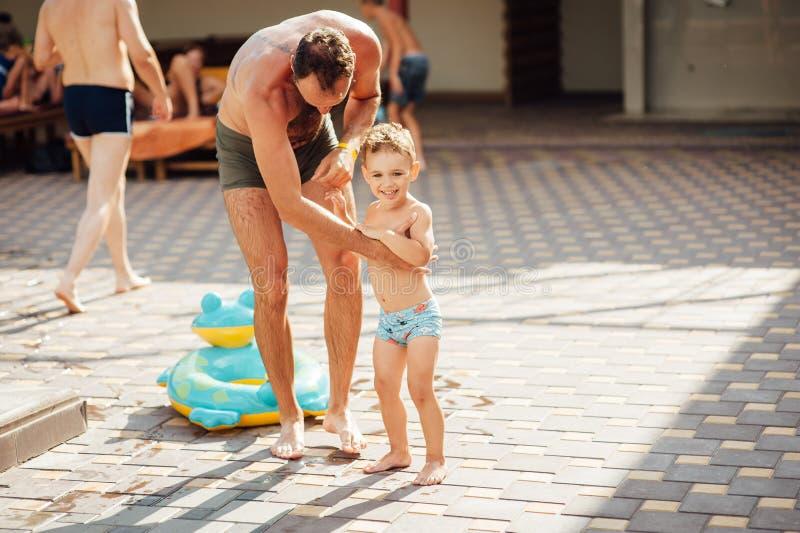 Padre e hijo divertidos en piscina de agua bajo luz del sol en el día de verano Ocio y nataci?n en los d?as de fiesta fotografía de archivo