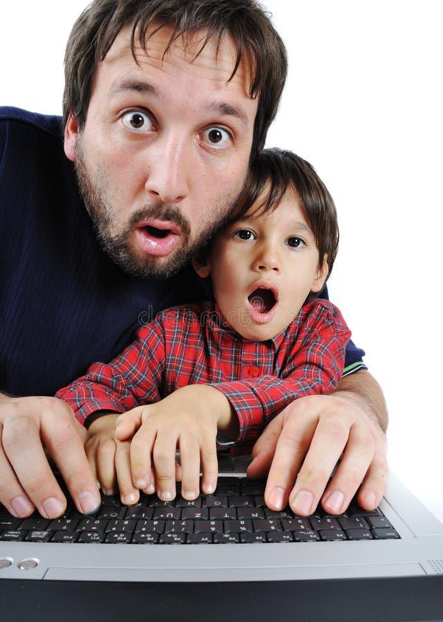Padre e hijo en la computadora portátil fotografía de archivo libre de regalías