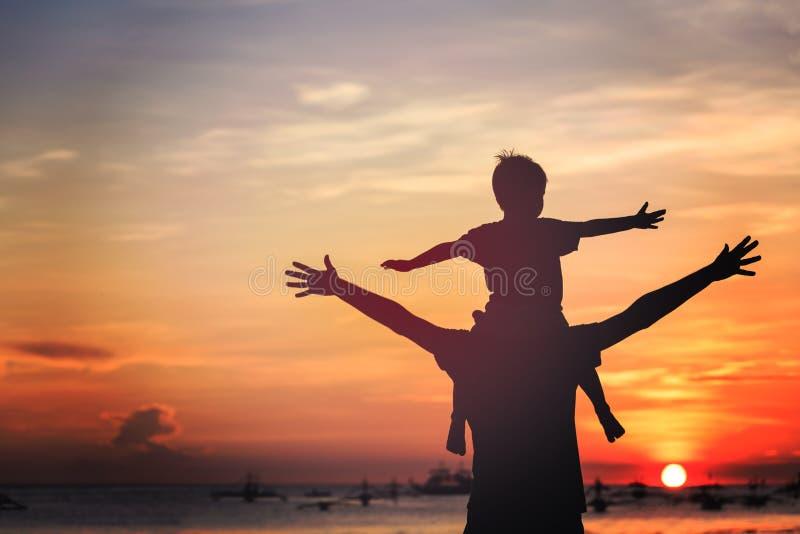 Padre e hijo en la playa de la puesta del sol fotos de archivo