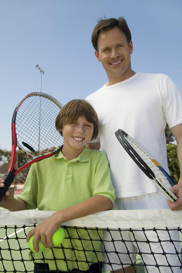 Padre e hijo en la red del tenis fotos de archivo