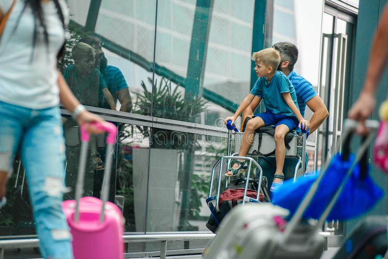 Padre e hijo felices y emocionados junto para el viaje, muchacho que se sienta y que anima en la carretilla del equipaje Vacacion fotografía de archivo libre de regalías