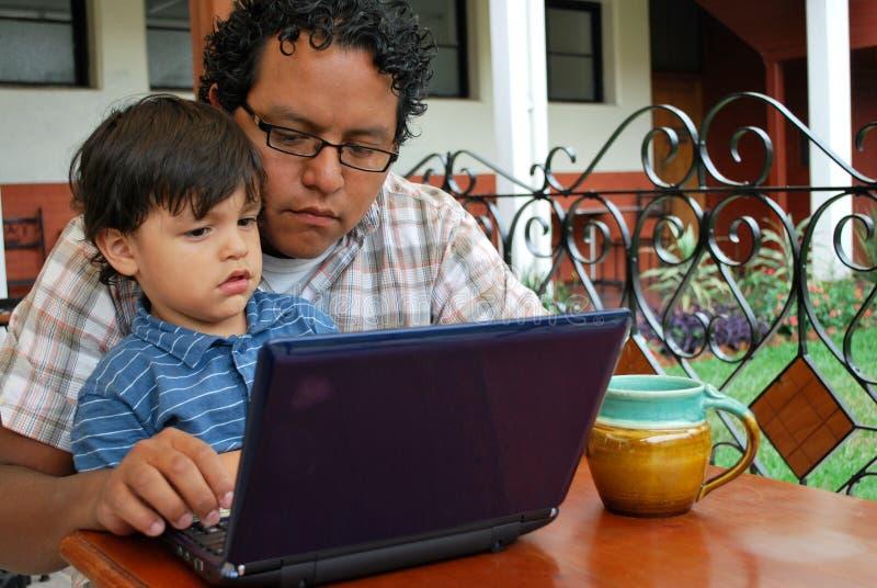 Padre e hijo hispánicos en la computadora portátil imágenes de archivo libres de regalías