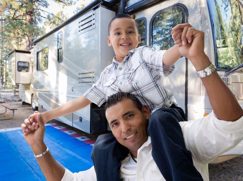 Padre e hijo hispánicos felices delante de su rv hermoso fotos de archivo