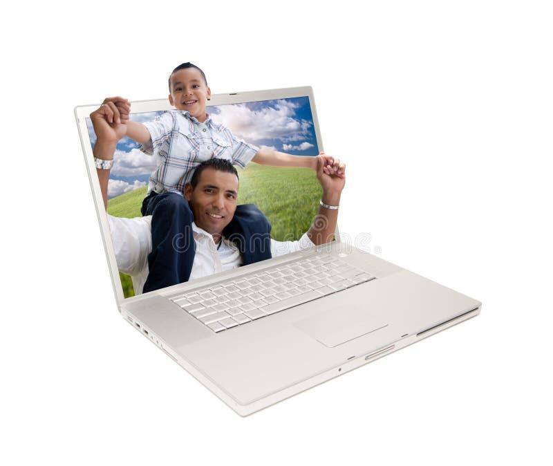 Padre e hijo hispánicos felices en pantalla de la computadora portátil fotos de archivo