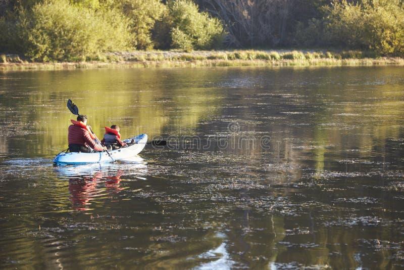 Padre e hijo kayaking en un lago, visión trasera, distante fotografía de archivo