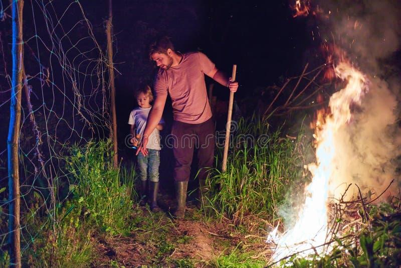 Padre e hijo, maleza ardiente de los aldeanos en el fuego en la noche, limpieza estacional del área del campo, forma de vida del  fotos de archivo