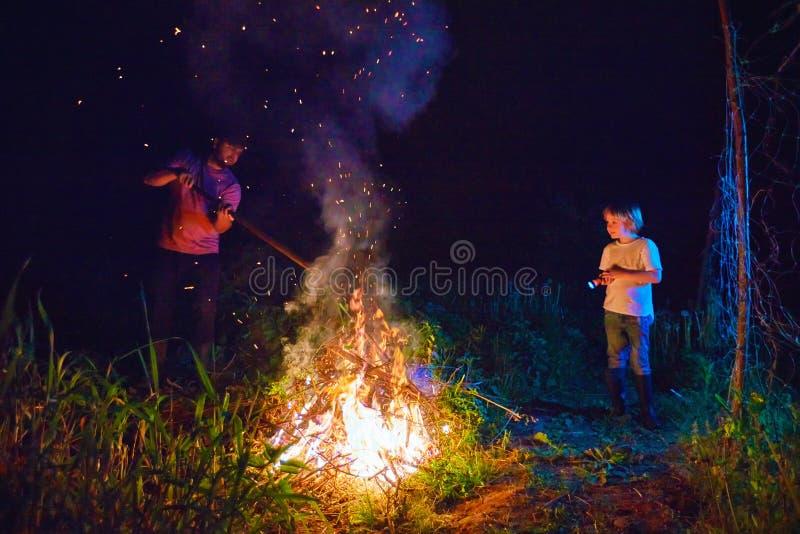 Padre e hijo, maleza ardiente de los aldeanos en el fuego en la noche, limpieza estacional del área del campo, forma de vida del  imagen de archivo libre de regalías