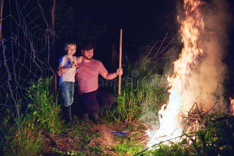 Padre e hijo, maleza ardiente de los aldeanos en el fuego en la noche, limpieza estacional del área del campo, forma de vida del  fotos de archivo libres de regalías