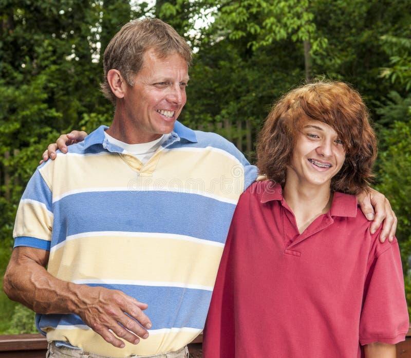 Padre e hijo - punky-mirando al adolescente con el pelo teñido largo - que ríen, divirtiéndose junto foto de archivo libre de regalías