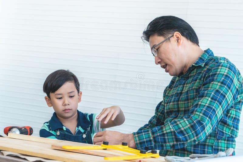 Padre e hijo que aprenden trabajar en el trabajo de madera con las herramientas para el concepto de la unidad de la familia fotos de archivo libres de regalías
