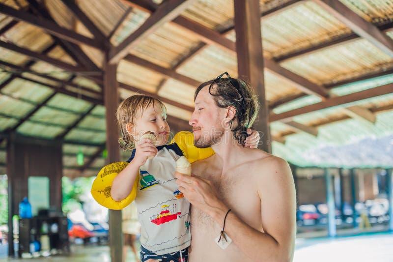 Padre e hijo que comen el helado en aquapark debajo de un tejado cubierto con paja imágenes de archivo libres de regalías