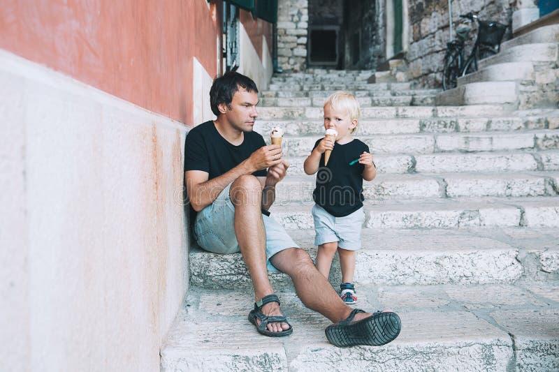 Padre e hijo que comen junto el helado al aire libre fotos de archivo