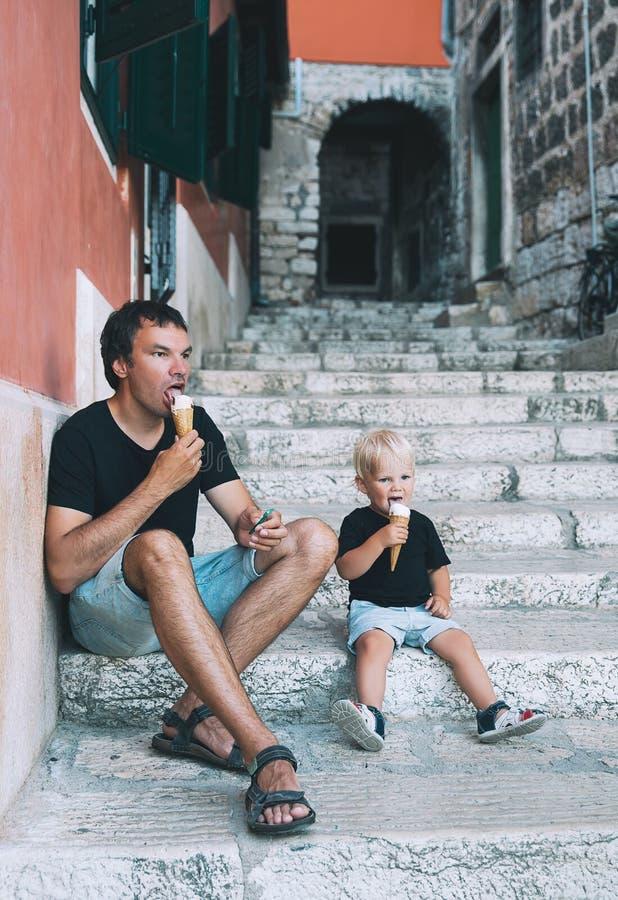 Padre e hijo que comen junto el helado al aire libre fotografía de archivo libre de regalías