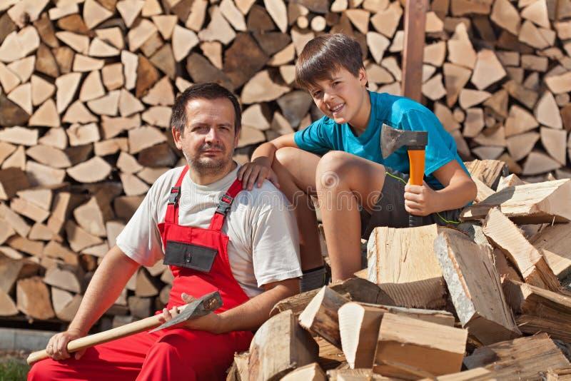 Padre e hijo que descansan sobre pila de madera tajada imagenes de archivo