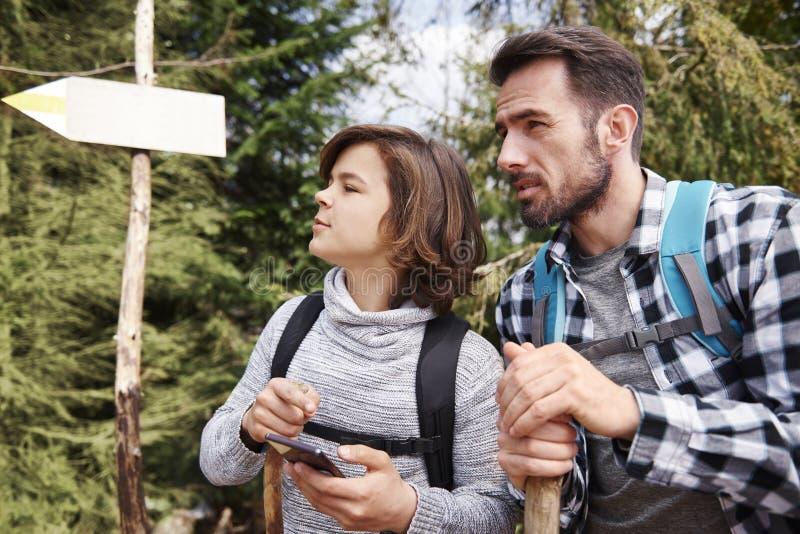 Padre e hijo que eligen el mejor sendero para caminar viaje imagen de archivo
