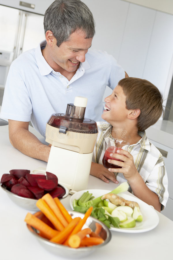 Padre e hijo que hacen el jugo de las verduras frescas fotografía de archivo libre de regalías
