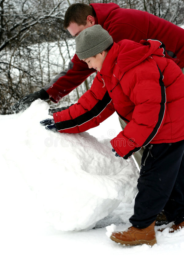 Padre e hijo que hacen el muñeco de nieve imagenes de archivo