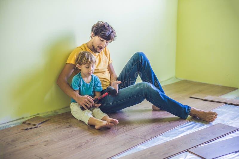 Padre e hijo que instalan el nuevo suelo laminado de madera infrarrojo imagenes de archivo