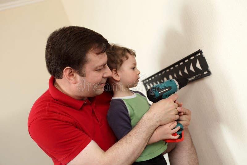 Padre e hijo que instalan el soporte TV fotos de archivo libres de regalías