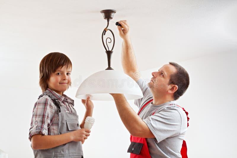 Padre e hijo que instalan una lámpara del techo fotografía de archivo