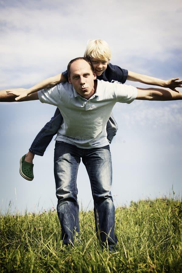 Padre e hijo que juegan al aire libre foto de archivo