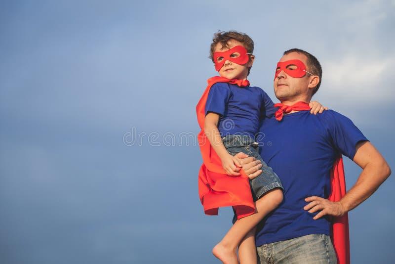 Padre e hijo que juegan al super héroe al aire libre en el tiempo del día foto de archivo