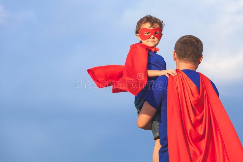 Padre e hijo que juegan al super héroe en el tiempo del día imagen de archivo