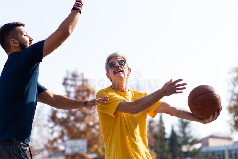 Padre e hijo que juegan a baloncesto en el parque imagen de archivo libre de regalías