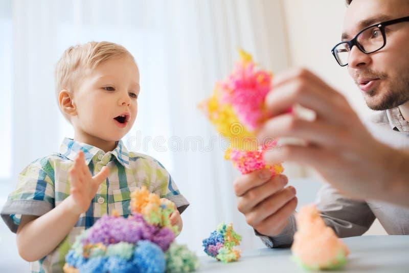 Padre e hijo que juegan con la arcilla de bola en casa fotos de archivo libres de regalías