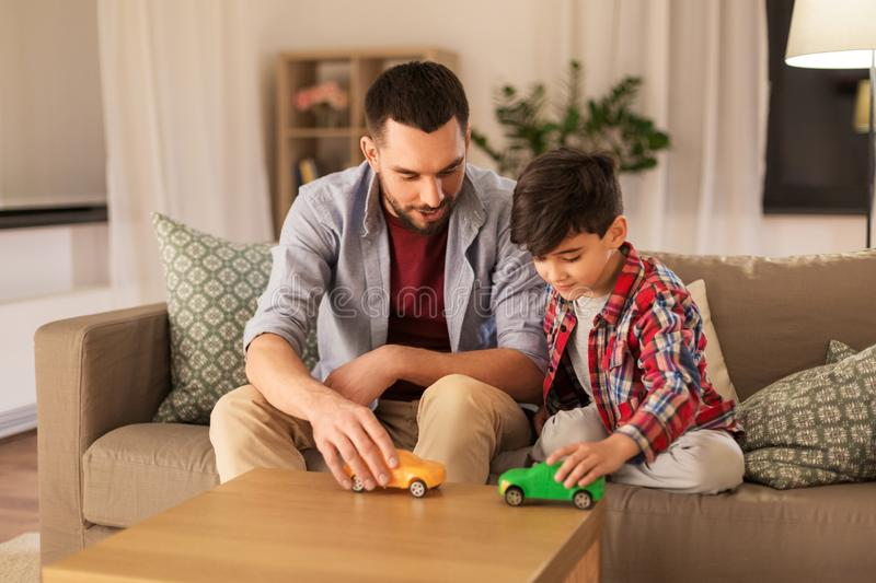 Padre e hijo que juegan con los coches del juguete en casa imagenes de archivo