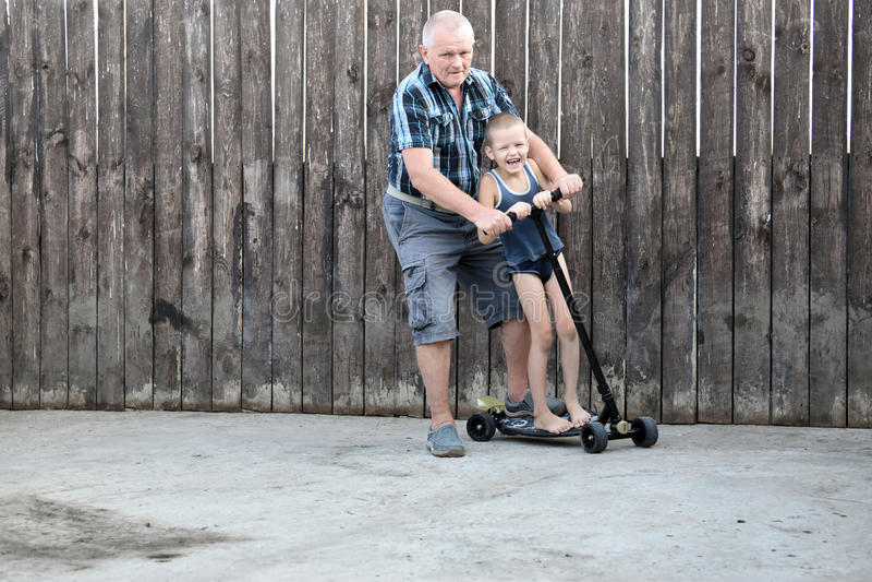 Padre e hijo que juegan en el camino en el tiempo del día Gente que se divierte al aire libre imagen de archivo libre de regalías