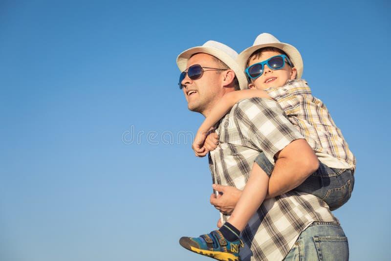 Padre e hijo que juegan en el campo en el tiempo del día fotos de archivo