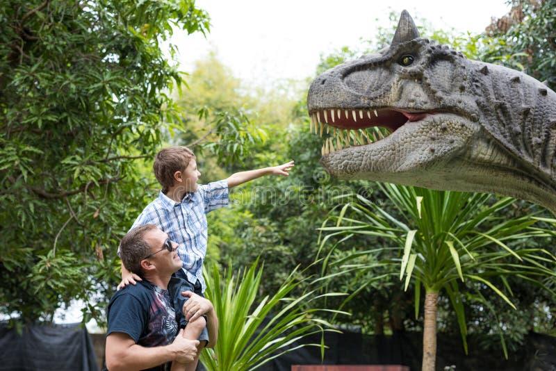 Padre e hijo que juegan en el parque de Dino de la aventura fotografía de archivo libre de regalías