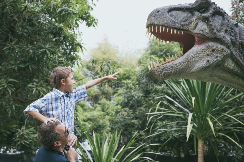 Padre e hijo que juegan en el parque de Dino de la aventura fotografía de archivo