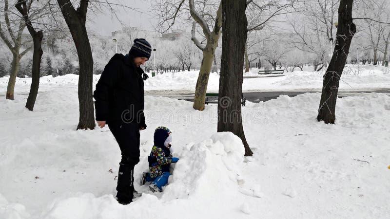 Padre e hijo que juegan en la nieve imagenes de archivo
