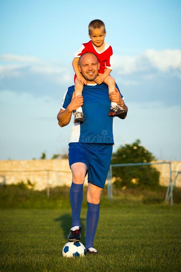 Padre e hijo que juegan a fútbol imagenes de archivo