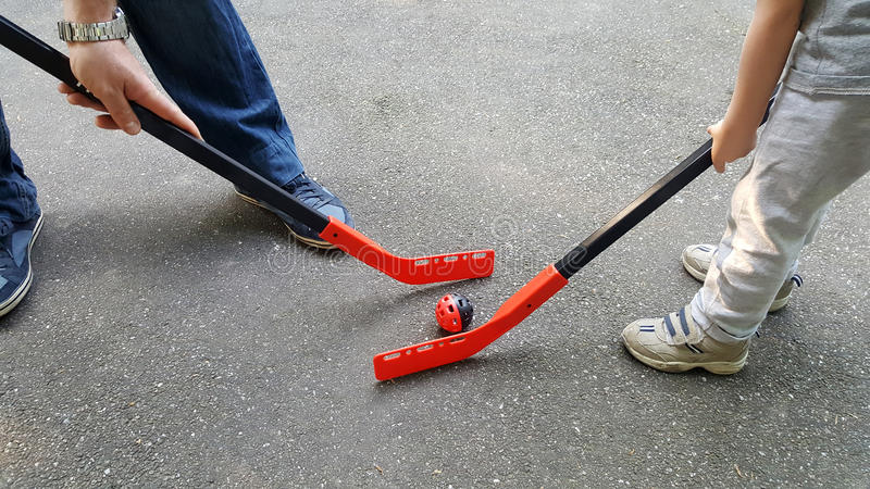 Padre e hijo que juegan a hockey al aire libre imagen de archivo libre de regalías
