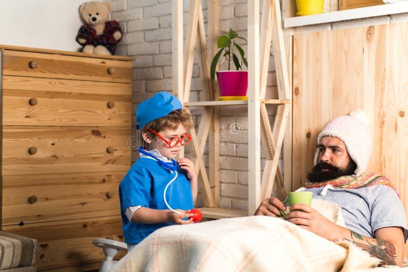 Padre e hijo que juegan la clínica en casa, concepto médico de la educación Doctor con el estetoscopio que examina al hombre barb foto de archivo