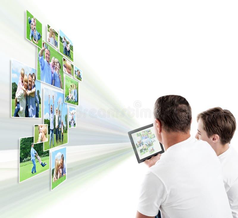 Padre e hijo que miran imágenes en la tableta fotos de archivo libres de regalías
