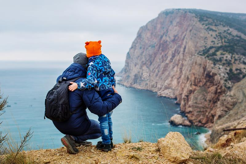 Padre e hijo que pasan tiempo así como la montaña y el mar hermosos foto de archivo libre de regalías