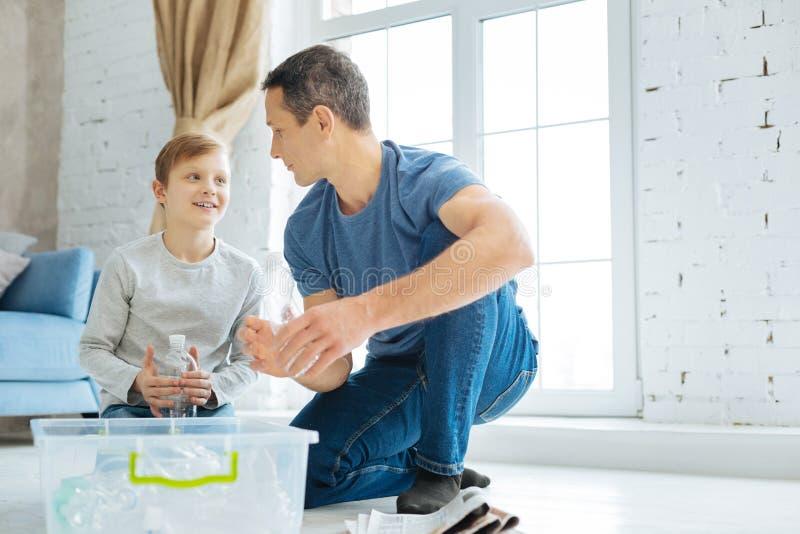 Padre e hijo que practican en el machacamiento de las botellas antes de reciclar foto de archivo libre de regalías