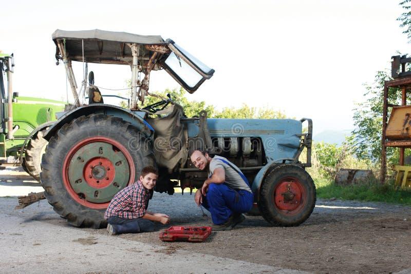 Padre e hijo que reparan un tractor imagen de archivo libre de regalías