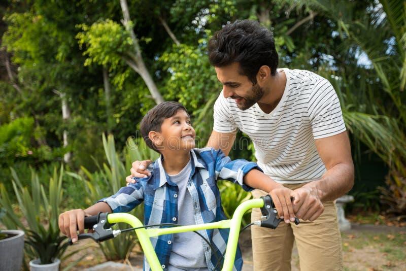 Padre e hijo que se colocan con la bicicleta mientras que mira uno a imagenes de archivo