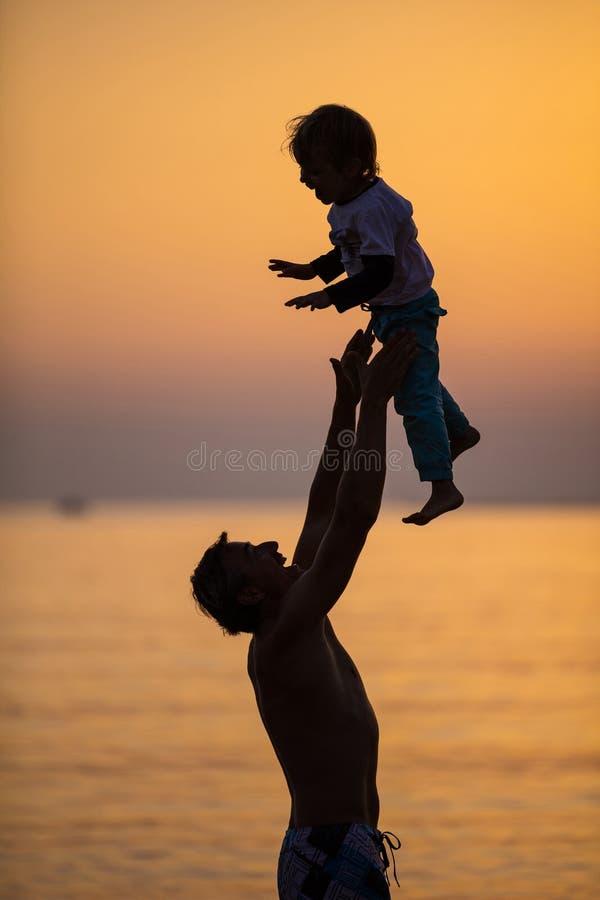 Padre e hijo que se divierten en la playa en la puesta del sol imágenes de archivo libres de regalías