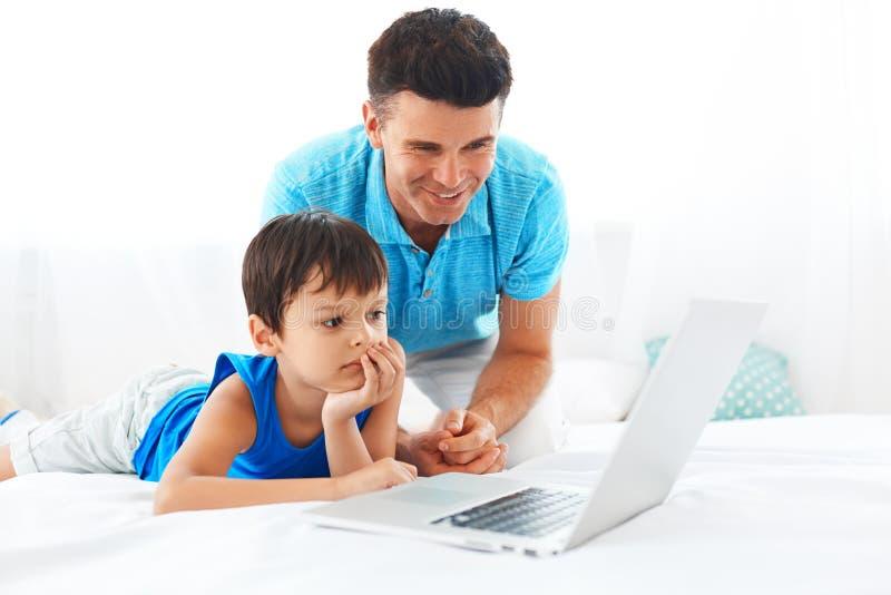 Padre e hijo que se divierten usando el ordenador portátil foto de archivo