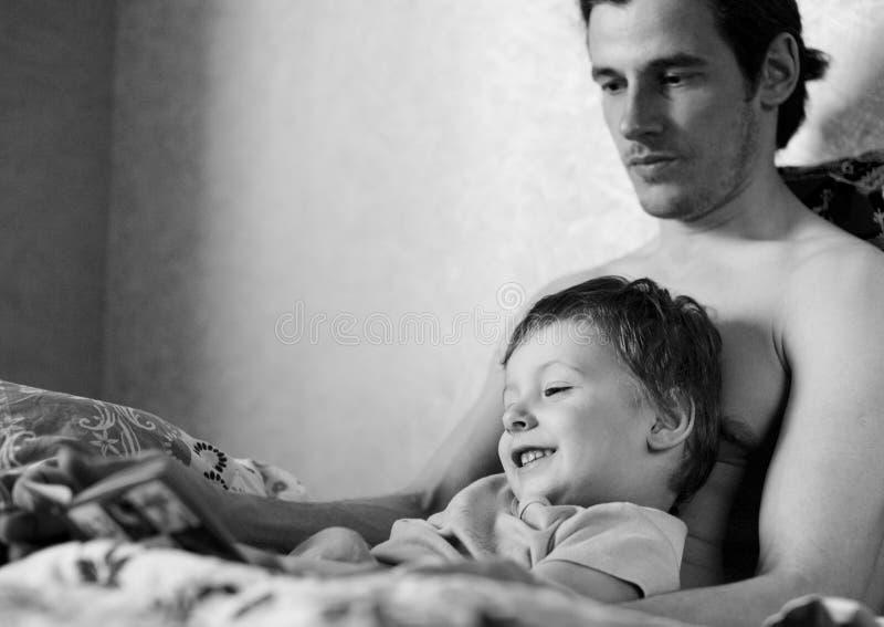 Padre e hijo que se relajan en la cama, libro de lectura imágenes de archivo libres de regalías