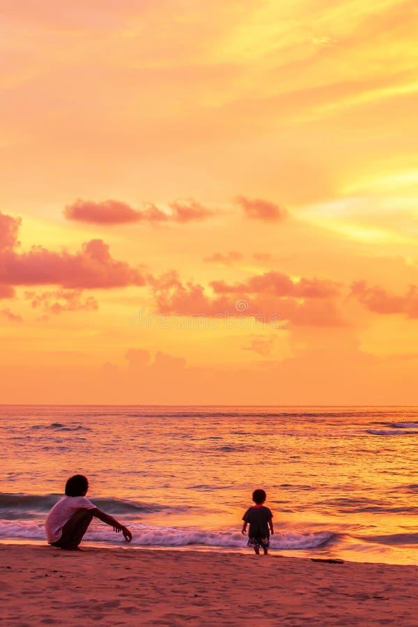 Padre e hijo que se relajan en la playa mientras que mira el cielo dramático de la puesta del sol imágenes de archivo libres de regalías