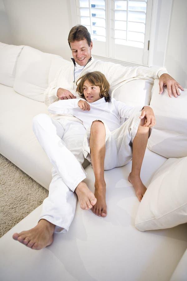 Padre e hijo que se relajan junto en el sofá blanco foto de archivo