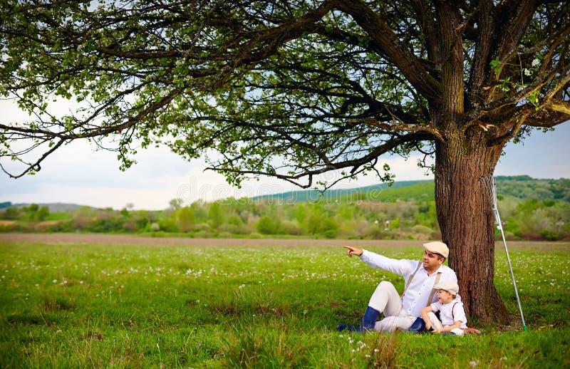 Padre e hijo que se sientan debajo del árbol, campo del granjero de la primavera imagen de archivo libre de regalías